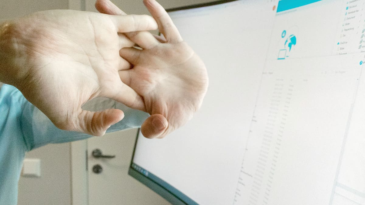Man taking a break and stretching hands in front of computer screen