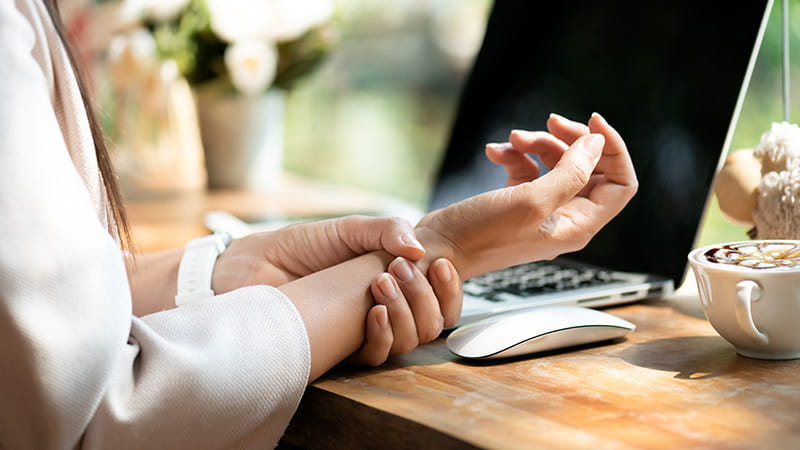 Woman with pain in wrist after working with computer